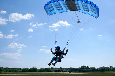 Man with a blue little canopy of a parachute is flies, close-up. High-speed landing of a Skydiver with parachuter against the background of clouds.  USA, Michigan