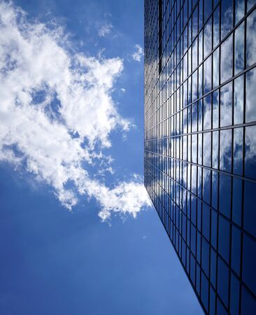 A low angle view. A white cloud in the blue sky next to a large building. Cloud reflected in mirrored glass. Chicago, Illinois