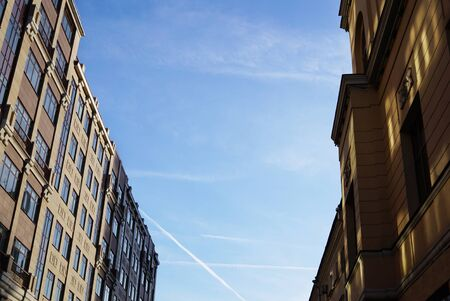 Street of Moskov, passage between ancient buildings, low angle view. Trace of a flying airplane in the sky. Russia, Moscow city