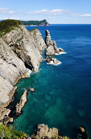 Blue sea deep and turquoise reefs in clear water near the shore. Rocks rise above the sea surface. Pacific Ocean, Far East of Russia, Vladivostok