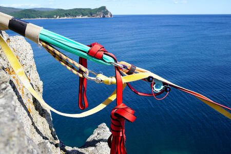 Part of climbing equipment on the background of the blue sea and island. Bright colored ropes and knots close up. Japanese Sea, Russia Archivio Fotografico