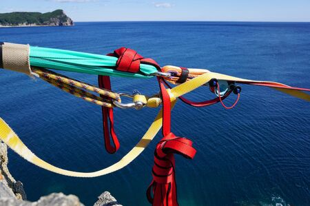 Part of climbing equipment on the background of the blue sea and island. Bright multi-colored ropes and knots close-up. Pacific Ocean, Russia, Vladivostok Stock fotó