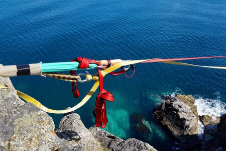Part of climbing equipment close-up on a background of blue sea. Bright colored ropes and knots. In clear water, a huge boulder. Slackline stretched between the rocks. Japanese Sea, Russia, Vladivostok