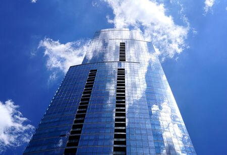 The building is from a low viewing angle close-up. White clouds are reflected in the window panes. The sun shines and the rays glares. Columns are located in the building's facade. Chicago, Illinois