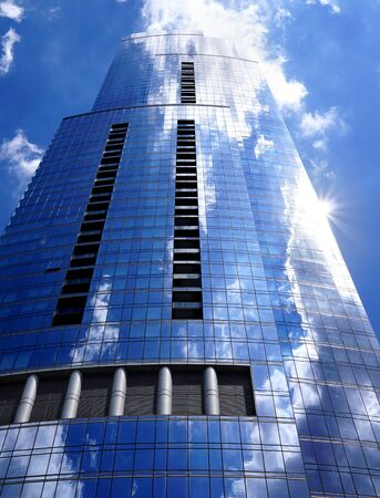The building is from a low viewing angle. White clouds are reflected in the window panes. The sun shines and the rays glares. Columns are located in the building's facade. Chicago, Illinois