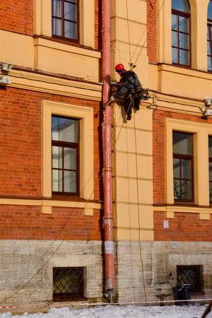Winter in Saint-Petersburg, a man cleaves icicles. Reklamní fotografie