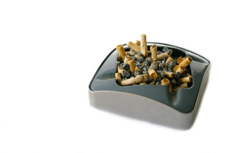 metal shtray full of cigarette butts, isolated on white background, stop smoking, bad habit. Warning picture on cigarette pack. Unhealthy living. Stock Photo