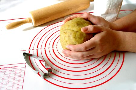 cooking and home concept, close up of female hands making cookies from fresh dough, carrot shaped cookie cutter on silicone mat. wooden rolling pin. Easter food. Photo for recipe.