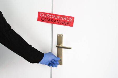 Coronavirus quarantine covid-19 red announcement on the sealed door, hand in blue rubber glove close entrance with key