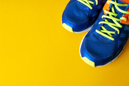 Blue sport shoes on yellow background, sport cloth, fitness at home, training ai quarantine time.