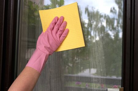 hand in rubber glove cleaning window with sponge. Wash glass. Housekeeping.