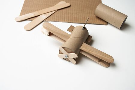 Aircraft from toilet paper roll and sticks. DIY for kids. Airplane toy, decoration children room. Recycling art.