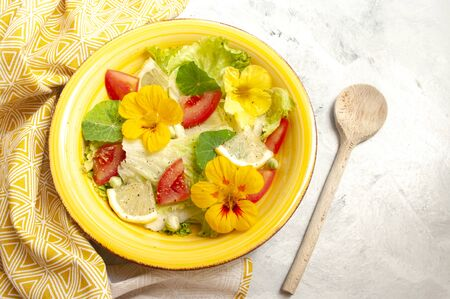 nasturtium flowers salad with tomatoes and lemones in yellow ceramic bowl. vegetarian food.Copy space. On grey background.