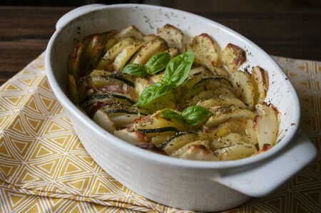 Casserole dish recipe.Hearty potato gratin bacon and zucchini,freshly served from the oven on a wooden table.