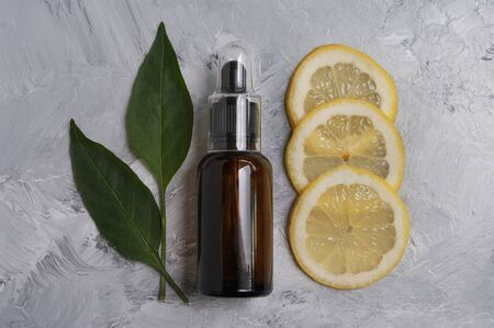 Dropper bottle, lemones, green leaves. Concept of natural cosmetic, organic ,essential oil.Copy space for text. Natural care. Aromatherapy