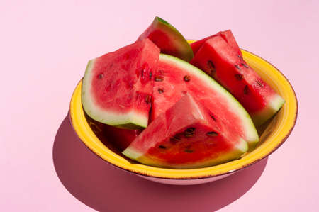 Fresh watermelon sliced in yellow bolw on pink background. Copy space. Summer fruit.