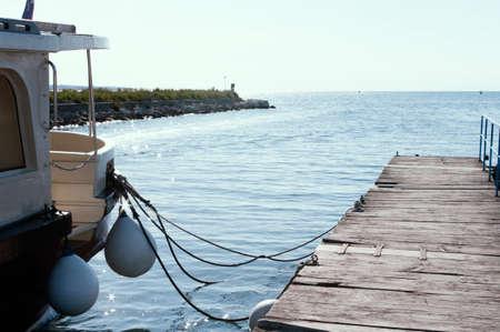 Adriatic sea , wooden pier and part of boat. Summer season.Slovenia.