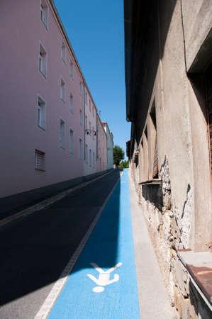 Narrow street with blue pedestrian path in Izola city, Slovenia. Deep view. 免版税图像
