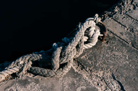 Marine knotted rope on pier close up. 免版税图像