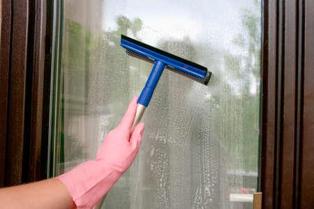 Wash windows on balcony doors. Housekeeping concept. 免版税图像
