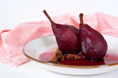 Poached pears in red wine with cinnamon. Sweet dessert with fruits,home made recipe. 免版税图像