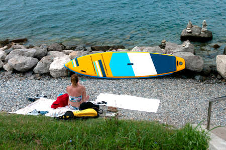 PORTOROSE, SLOVENIA - AUGUST 29, 2020: Young woman on the beach near sea with sup . Portorose, Slovenia.