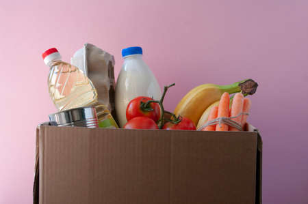 Cardboard box with grocery. tomatoes,bananas,milk,eggs in paper box, carrot, cannedfood bottled oil. Shopping online.