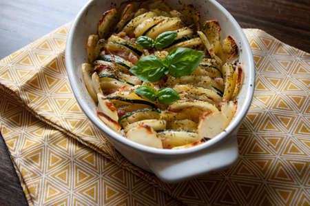 Hearty potato gratin bacon and zucchini,freshly served from the oven on a yellow tablecloth.