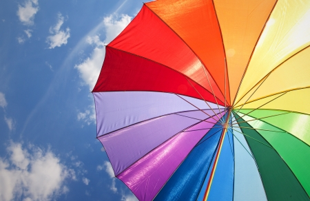 Rainbow umbrella on sky background