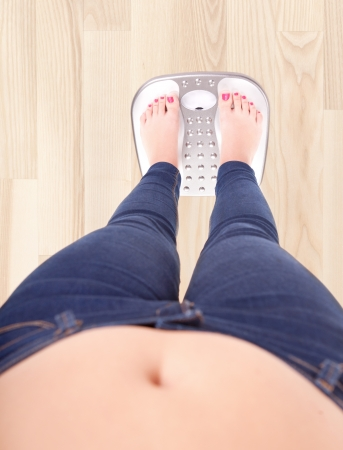 over weight: Woman on a bathroom scale - diet and overweight concept Stock Photo