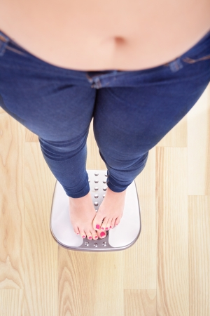 overweight: Woman on a bathroom scale hiding the numbers - diet and overweight concept  Stock Photo