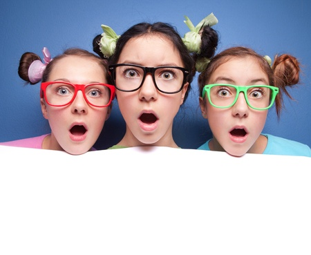 nerd girl: Three amazed teens with blank presentation board Stock Photo