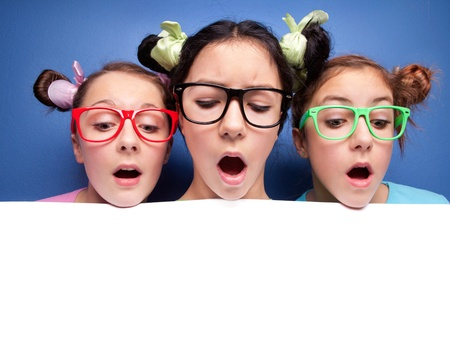 surprised child: Three amazed teens with blank presentation board Stock Photo