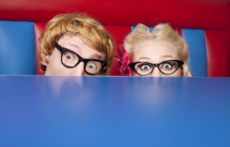 Nerdy couple hiding behind a table  photo