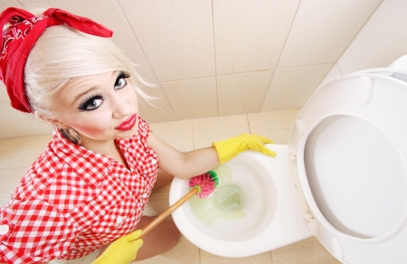 Attractive girl cleaning toilet photo