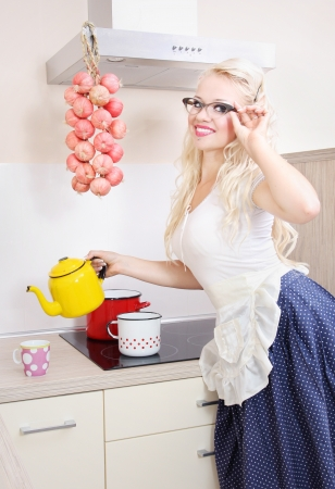 Cheerful housewife pouring tea photo