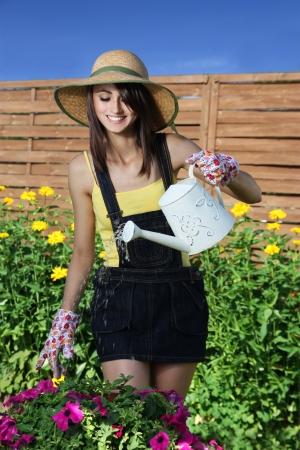 Cheerful girl watering flowers