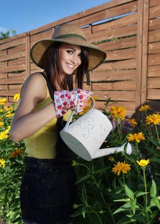 regar las plantas: Mujer atractiva joven que está regando las plantas