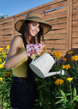 Young attractive woman is watering plants photo