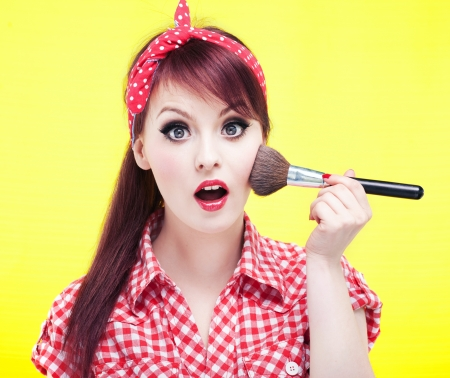 pin up: Cute pin up girl applying blusher  Stock Photo