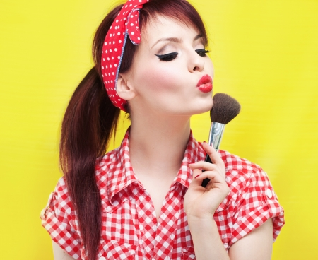 pinup girl: Cute pin up girl applying blusher  Stock Photo
