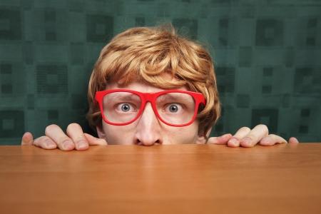 peaking: Scared nerd hiding behind a desk