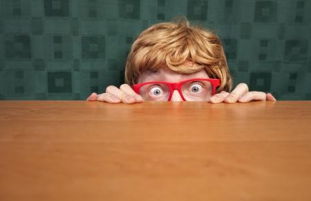 scared man: Scared nerd hiding behind a desk