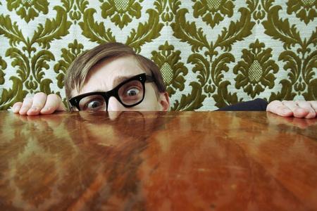 Scared nerd hiding behind a desk photo
