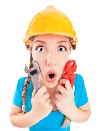 home improvement store: Surprised woman wearing a hardhat holding pliers and spanner