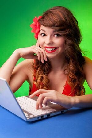 Colorful portrait of smiling young woman working on a laptop photo