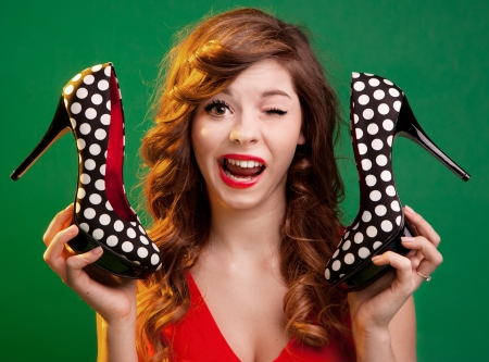 Funny young woman holding high heels shoes  photo