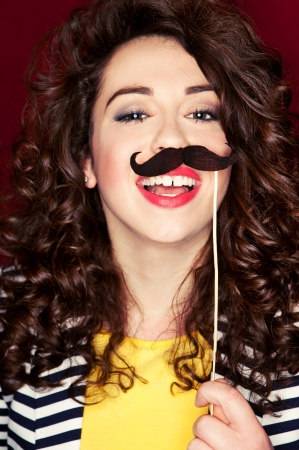 moustache: Attractive playful young woman holding mustache on a stick Stock Photo