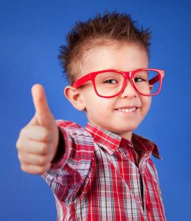 Cheerful five years old boy with thumb up  photo