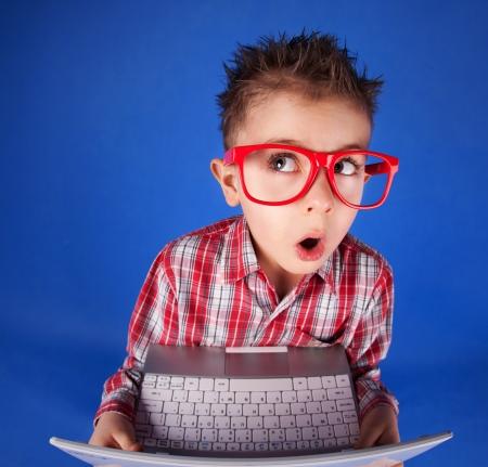 cara sorprendida: Niño pequeño con un ordenador portátil, concepto adicción a la computadora Foto de archivo